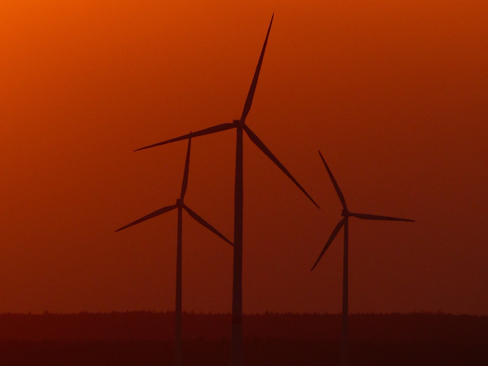 renewable energy wind turbines at sunset