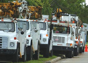 Electric company trucks line Spruce Creek Road Monday morning, August 16, 2004